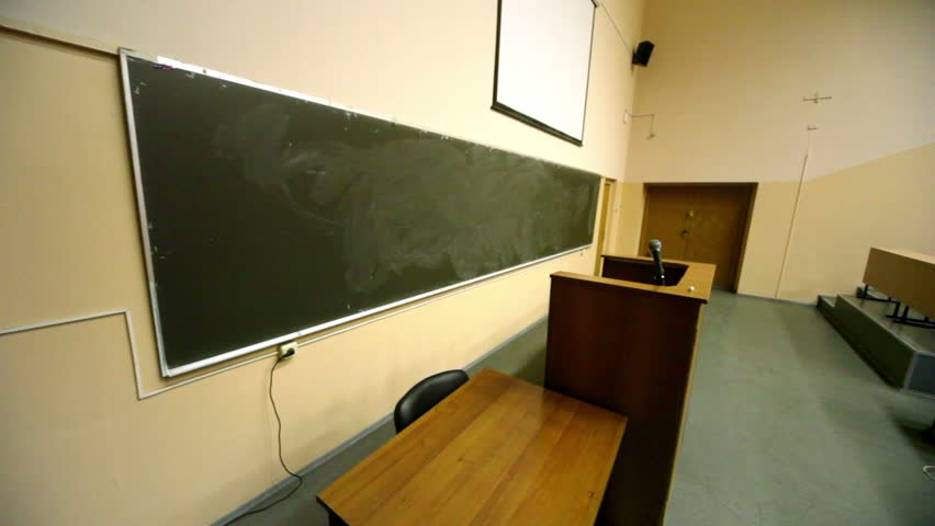 Empty lecture theater, white screen above blackboard, tribune with microphone, wooden furniture on several levels