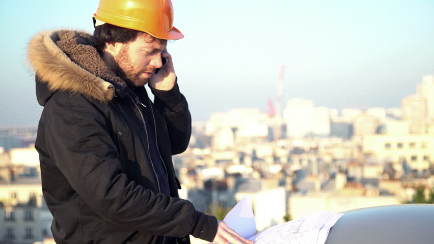 Paris, France - January 21, 2016: Building contractor looking at blueprints at constuction site | Shutterstock HD Video #16997824