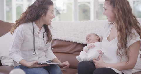 4K New mother with baby daughter talking to health visitor at home UK - April, 2016