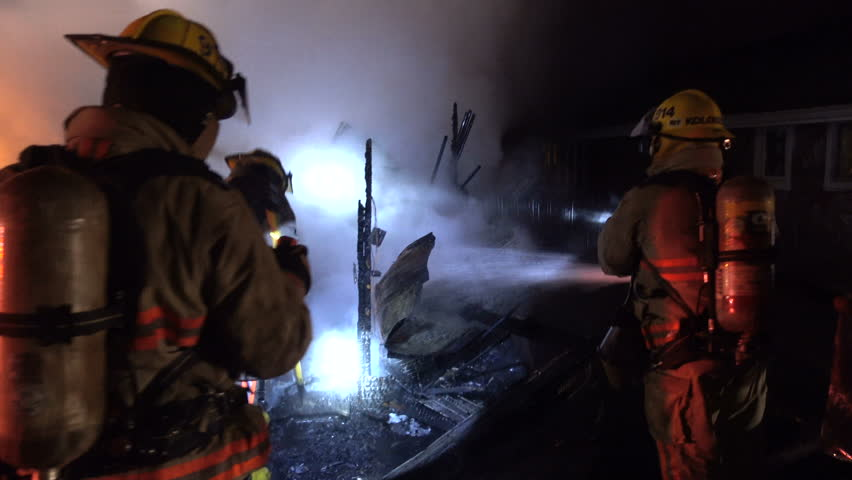 Firemen examine and spray smoking remains of burnt building. Fire is extinguished, but water is sprayed on the ashes by fire response team to snuff out embers that might relight. Rear view of firemen.