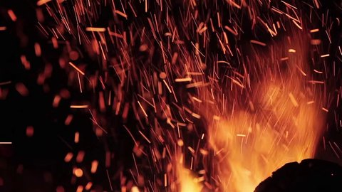 Extreme close up of fire sparks moving on dark night sky as black background coming from brightly burning warm outdoors bonfire in forest