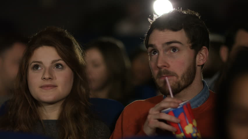 4K Young couple watching film in busy movie theatre. Audience puts on 3D glasses as the film begins. Shot on RED Epic. UK - April, 2016 #17053504