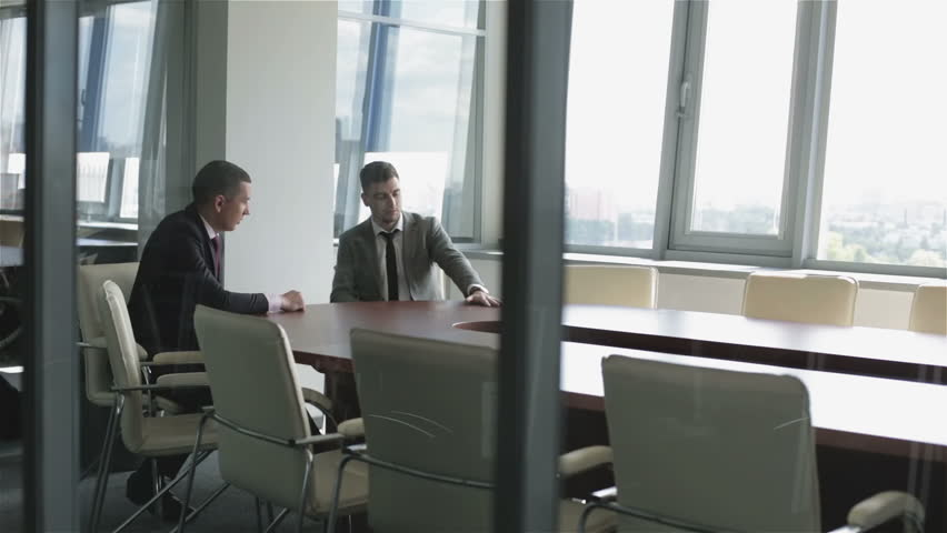 Two businessmen are sitting at a table in a room behind a glass wall. Businessmen in suits are discussing new project in a meeting room.