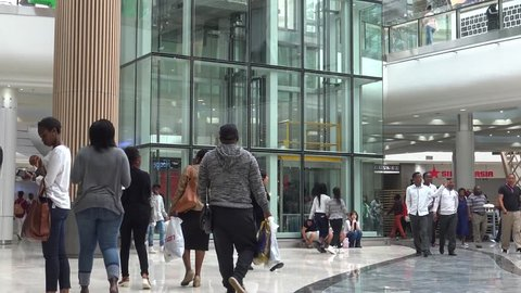 JOHANNESBURG, SOUTH AFRICA - 7TH MAY 2016: Hundreds of shoppers of various ethnic backgrounds walk through the newly opened Mall of Africa in Johannesburg. An elevator can be seen in the background.