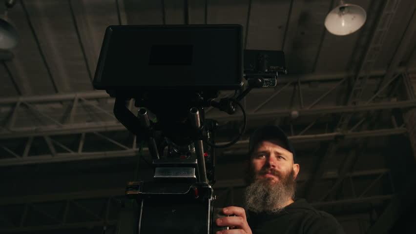 Low shot of camera operator panning professional camera in dark studio | Shutterstock HD Video #17067214