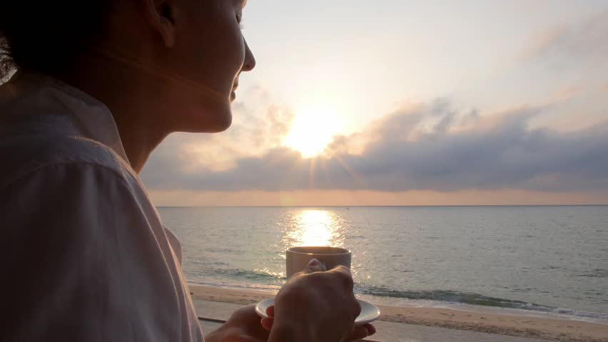 Woman Taking a Sip of Coffee in Beach Restaurant by Sea