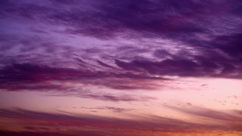 Clouds, fast moving with purple, pink, blue and the reddish hues of a deep
