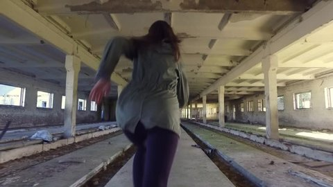 The girl run away from killer in abandoned building through the hallway. Back view horror dark mood. Steadicam shot. Smooth tracking. Old abandoned place. Slow motion.