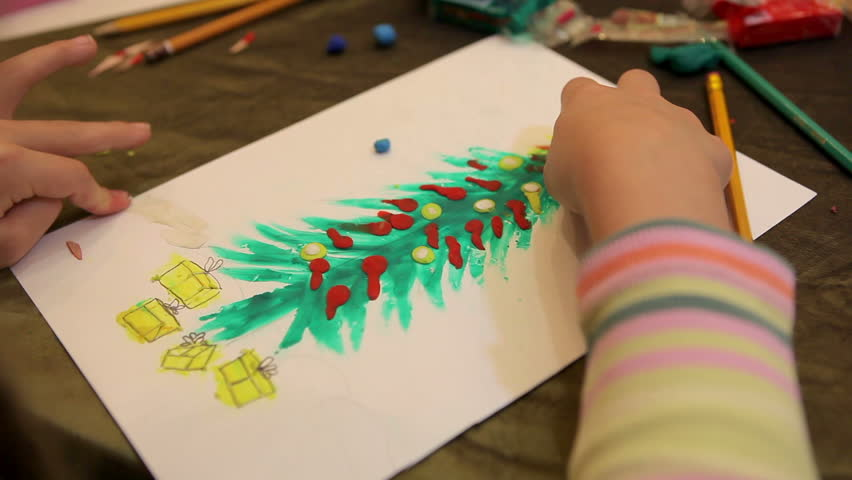 Close up of a childs hand draw christmas fir-tree from plasticine.