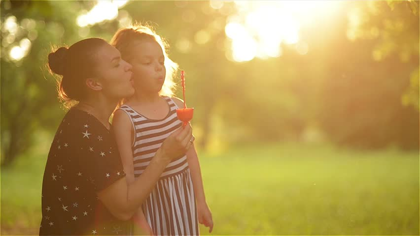Beautiful mother with her daughter in nature making soap bubbles and laughing | Shutterstock HD Video #17150434