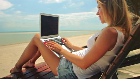 Young woman sitting at the sunbed with a laptop in front of sunset view. Lady freelancer working at the beach.