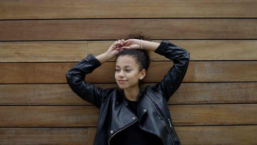 Young african american woman posing outdoors over wooden background. Trendy and urban style.  | Shutterstock HD Video #17173876