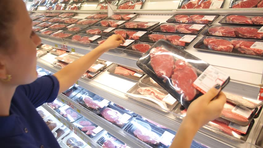 Young Woman Choosing Meat in Supermarket