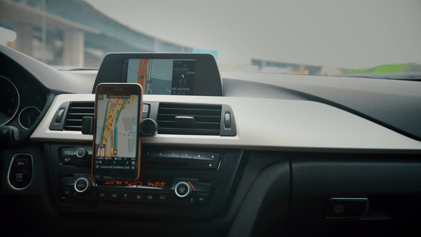 Close up on screen navigation tracking vehicle location and route while driving on road. GPS navigation on smartphone showing route.