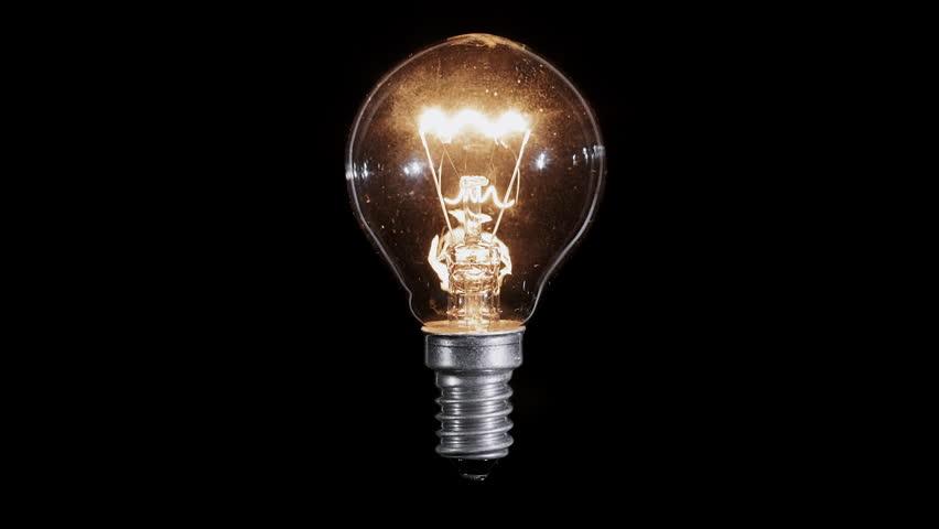 Lamp light bulb twinkles over black background, macro view, loop ready