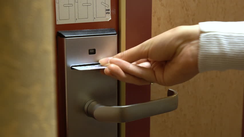 A young woman opens the door of his hotel room using an electronic key card.