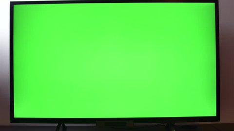 Left Handed Man Surfing The Channels Of A Green Screen TV Set