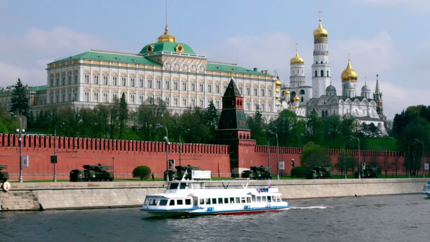 Antiaircraft motorcade ride by quay of Moscow Kremlin, ships sail down the river, red brick walls and Ivan Great Bell Tower. Victory Day 1945 year. Russia.