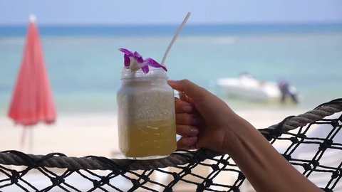 Female Hand with Fresh Pineapple Juice in Hammock on Beach.