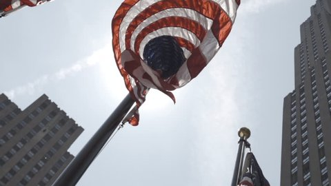 A patriotic American Flag blows in the wind in slow motion at 240 fps. The flags fly outside of New York City's Rockefeller Center. New York - May 1, 2016