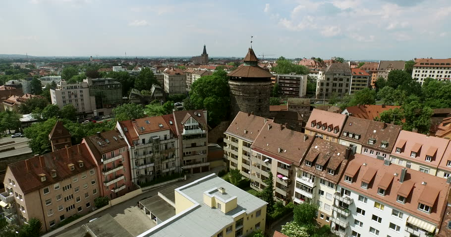 NUREMBERG, GERMANY June 6, 2016: The old city is filmed in an aerial shot starting at the city walls and flying then over the old city with all its houses, markets and parks.