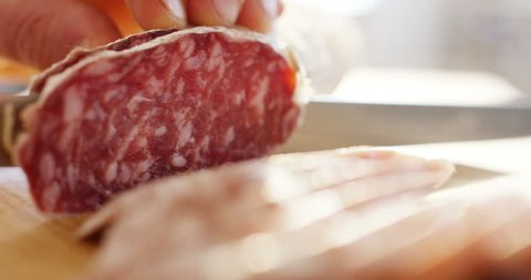 hand expert cuts Parma seasoned salami, thinly sliced with a knife and emanates the taste and the Italian flavor