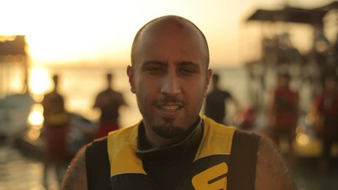 Bahrain - circa 2011 - MCU handheld portrait of a Bahraini man standing by the seaside at sunset. Men on jet skis are in the water behind him.