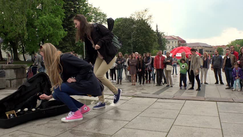 VILNIUS, LITHUANIA - MAY 21, 2016: Playful girls give money for true hearted boys playing music and singing on street music day on May 21, 2016 in Vilnius, Lithuania. Panorama shot. #17378734