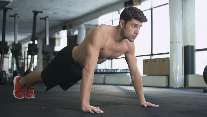 Handsome fitness man doing push ups in gym