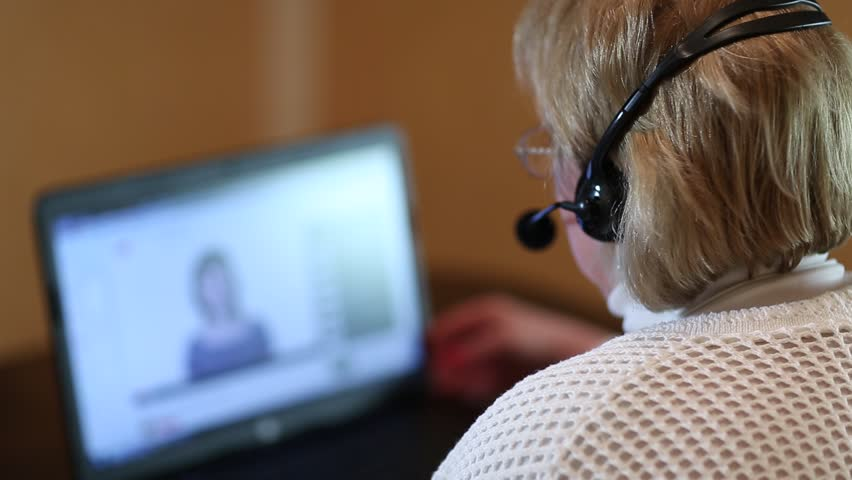 Woman with headphones with microphone talks to a customer via computer. Woman with pc communicates through skype. Woman with laptop. Senior woman with headphones and notebook speaks with customer