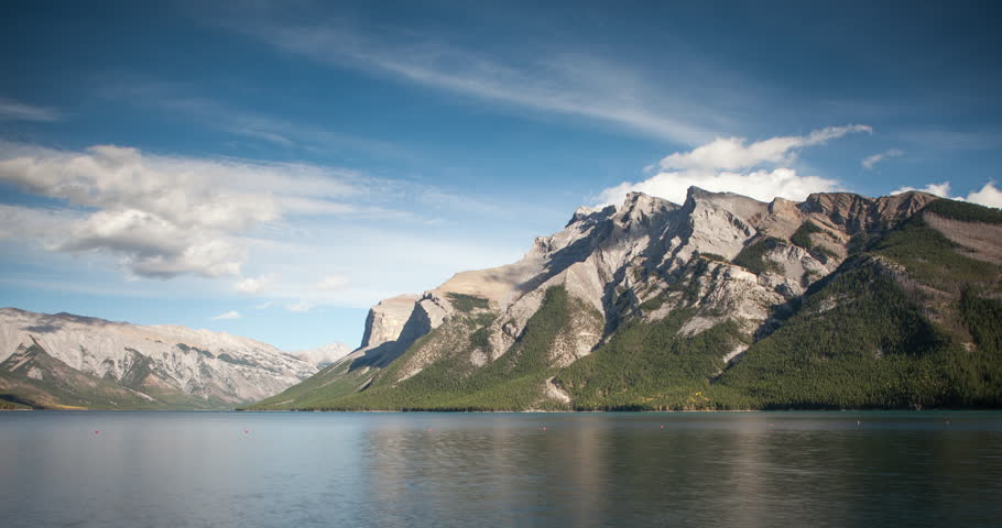 Banff National Park, Alberta, Canada - Lake Minnewanka with Mountains and forest at lakeside and clouds at blue sky - Timelapse with motion - October 2014