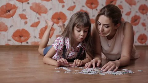 little girl collects puzzles with mom lying on the floor