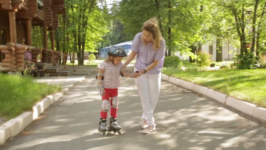 mom teaches little daughter to roller skate in the Park