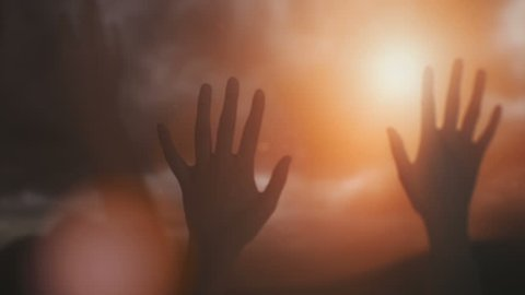 Silhouettes of hands raised in worship with sunlight.