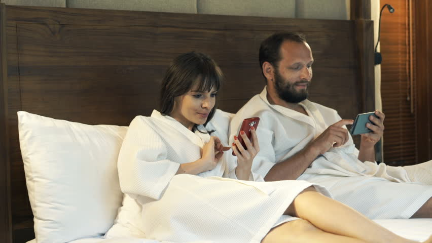 Young couple in bathrobe using smartphone in the bedroom   HD stock footage  clip. Young Couple In Bathrobes Watching Movie On Tablet Lying On Bed At