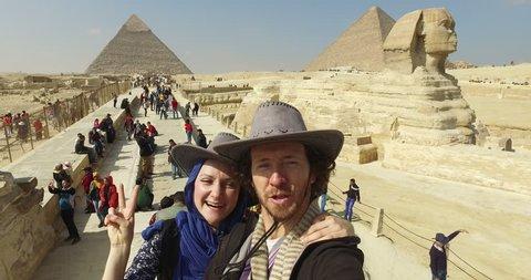 CAIRO, EGYPT - FEBRUARY 04, 2016: Tourist couple taking selfie at Giza pyramids complex