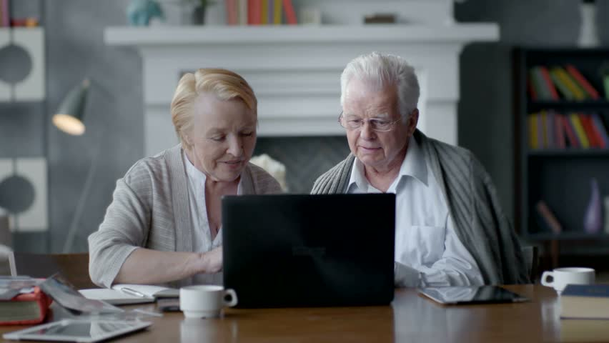 Web Camera, Elderly couple having fun in communicating with family on the internet in comfortable living room
