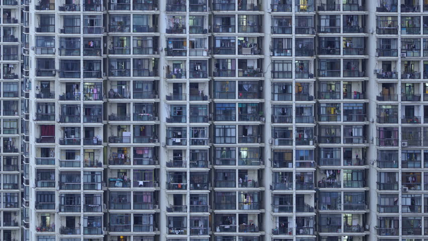 Timelapse of apartment windows at dusk to night. Nighttime time lapse of illuminated building windows at night with people living in flats with balcony in Shanghai, China.