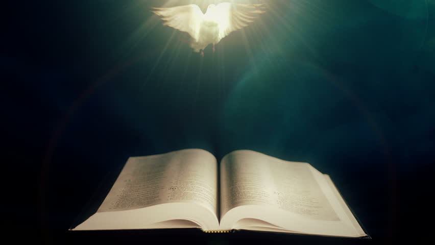 Holy Bible with Dove of Peace illuminated by a beam of light.