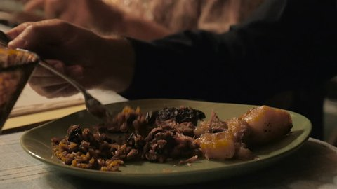 Close up of a man eating from a dinner plate including meat, potatoes, and rice