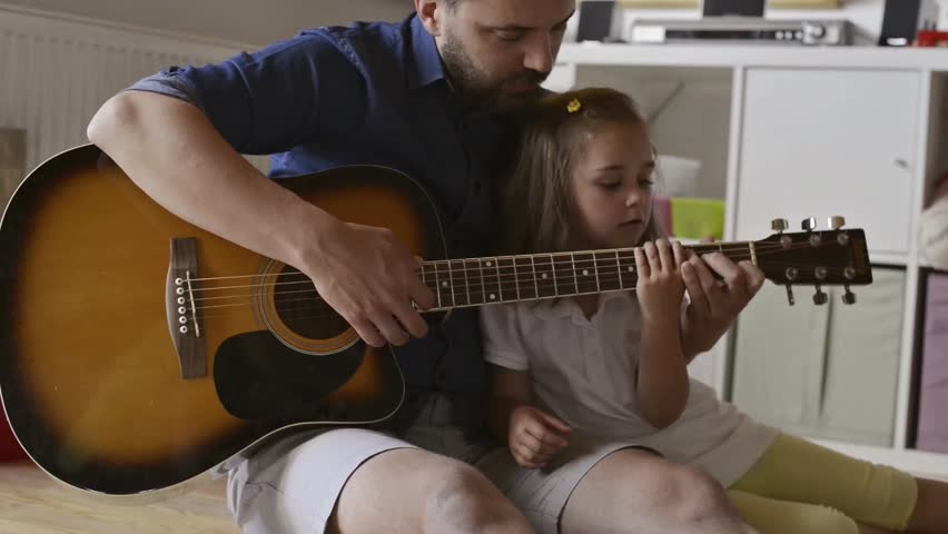 Father and daughter playing guitar, sitting on the floor #17531284