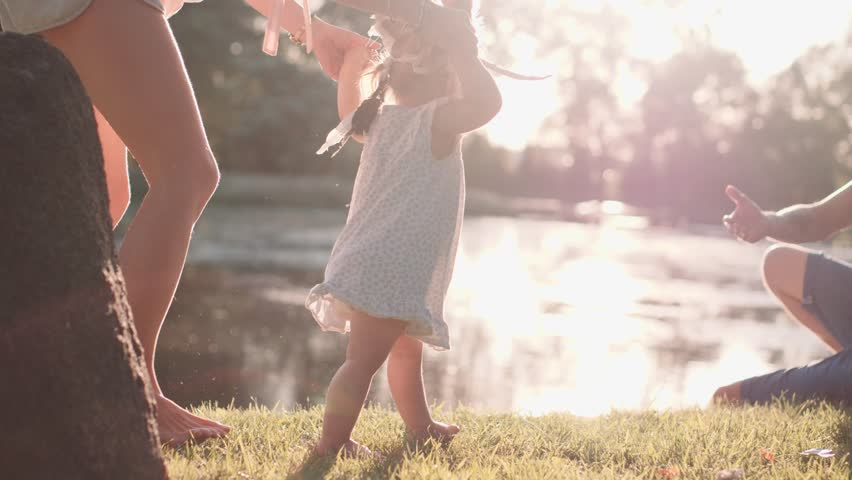 Little baby learns to walk. First Steps. Slow Motion 120 fps, 4K. Parents are teaching their child to do the first steps on a green grass in summer. Happy childhood and Parenthood concept. Family love | Shutterstock HD Video #17554444
