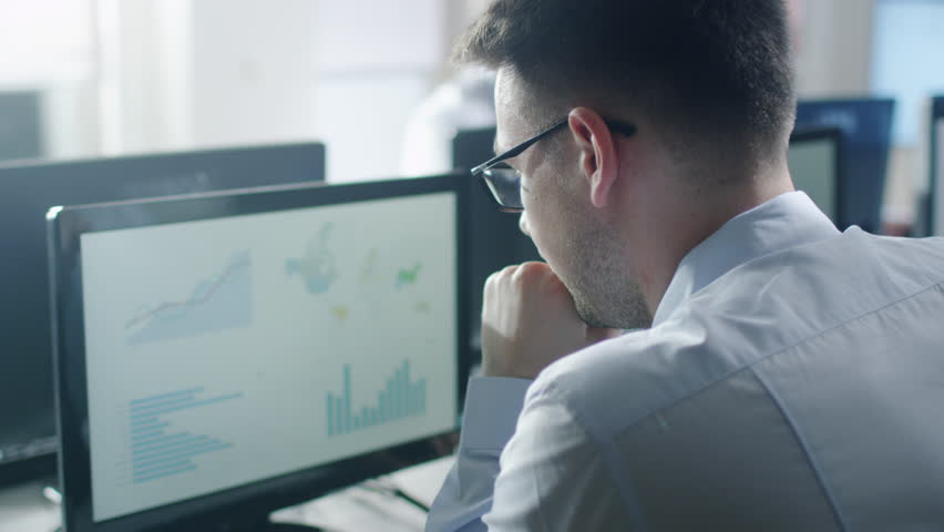 Team of Professionals Working at the Computers in Bright Office. Man Working with Charts. Shot on RED Cinema Camera in 4K (UHD). | Shutterstock HD Video #17607364