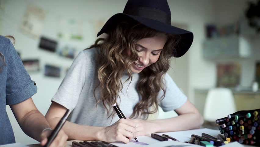 Designers draw sketches in the Studio. two attractive women working and smiling. Workspace designer. White sheet of paper, pencils, markers, felt-tip pens.