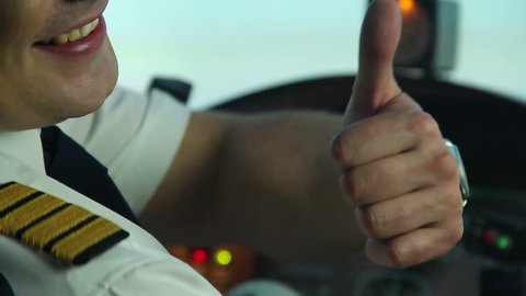 Happy professional pilot in cockpit showing thumbs up sign, enjoying his work. Professional airplane commander getting ready for taking off, nobel occupation, aviation. Happy aircraft crew member