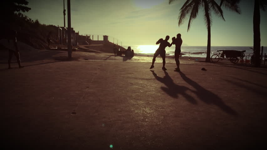 Dark gritty silhouettes of boxers fighting in slow motion cast long shadows against the morning sun at Arpoador in Rio de Janeiro, Brazil #17650774