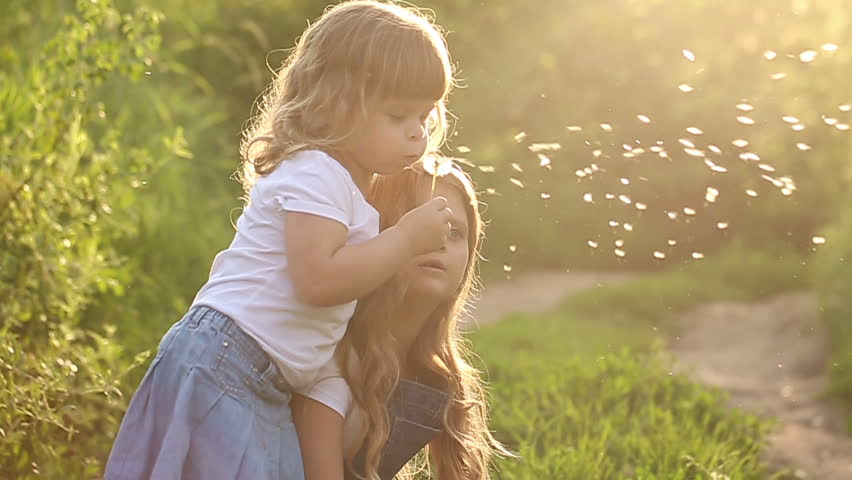 Two little sister are blowing on a dandelion. Rest at nature. Slow motion