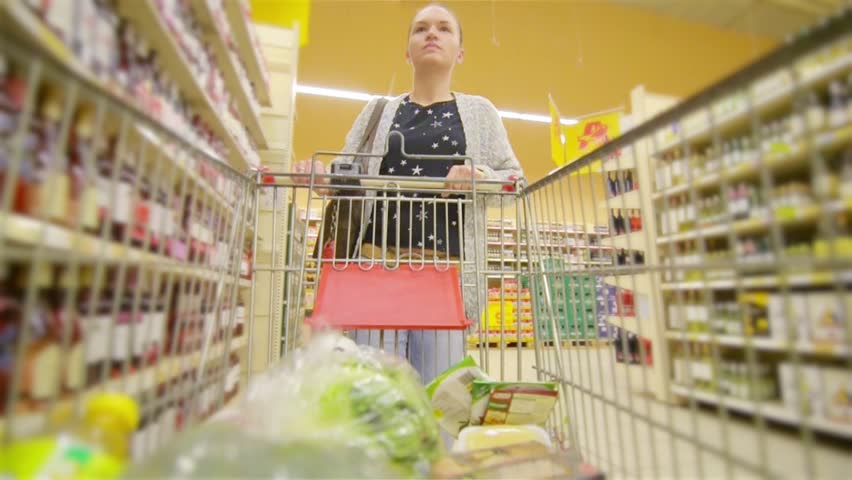 Caucasian woman walking along wholesale shelves and taking goods in shop trolley, beautiful young wife shopping in a supermarket | Shutterstock HD Video #17686003