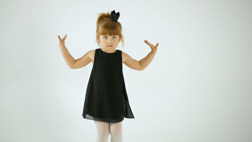 Cute Little Girl In Black Dress Dancing And Having Fun, Isolated On White
