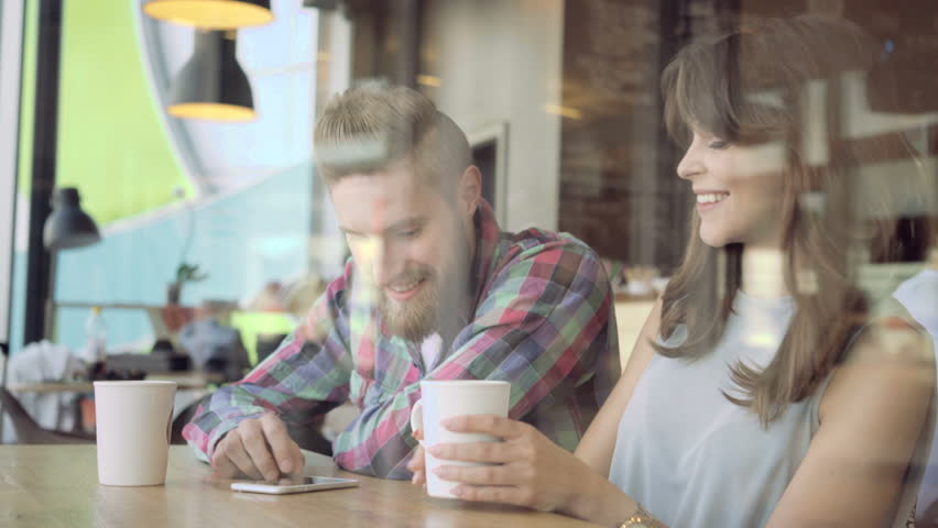 Attractive young couple using smartphone at cafe